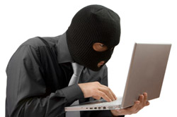 Man in a black mask on a laptop