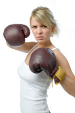 Woman with boxing gloves on ready to throw a punch
