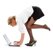 A woman crouching in front of a laptop computer